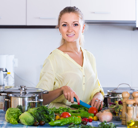 kitchen spanish: smiling spanish housewife cooking vegetables at domestic kitchen