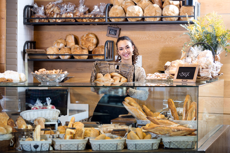 smock: Positive female staff selling fresh pastry and baguettes in local bakery