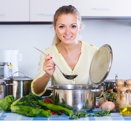 kitchen spanish: happy spanish housewife cooking vegetables at domestic kitchen