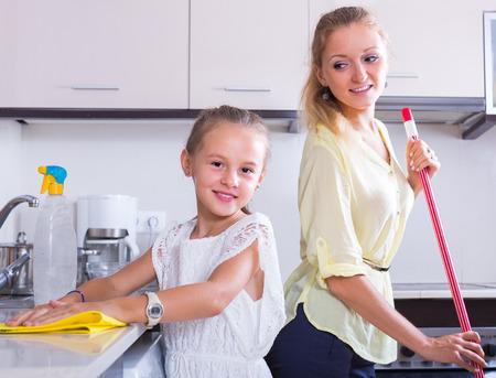 diligente: ni�a diligente para ayudar a limpiar la madre sonriente en la cocina en el hogar