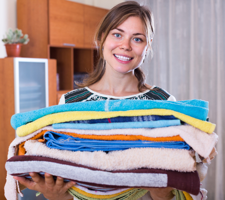 doing chores: Lovely young woman with colorful towels after laundry indoors
