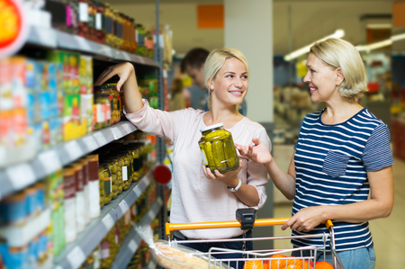 canned goods: Cheerful women customers standing near shelves with canned goods at store. Focus on the young woman