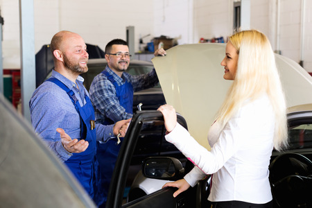 25s: Two troubleshooters showing fixed car to friendly client Stock Photo