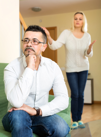 nagging: Husband is sitting on a sofa tired of his wife and turned away from her. His wife is nagging him