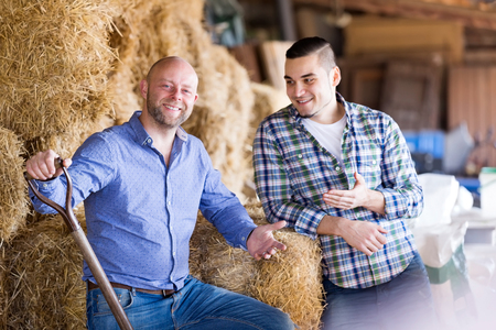 hayloft: Two smiling farm workers working in the hayloft. Focus on the left man