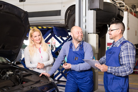 25s: Two happy mechanics examine a broken car at a repair shop in front of its female owner Stock Photo