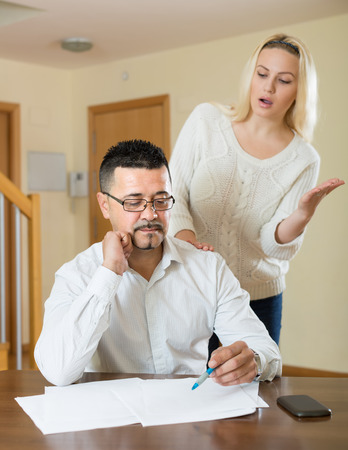 Family conflict over financial documents in the living room at home. Focus on man