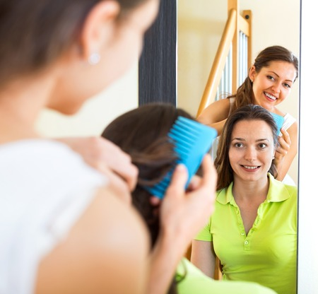 cognate: Young smiling girl doing hairstyle for her girlfriend