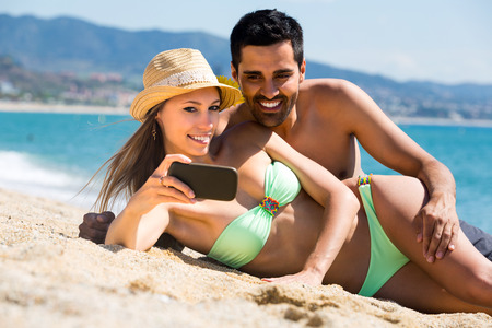 taking a wife: Beautiful wife and handsome husband taking a self portrait lying on sand on beach near sea Stock Photo