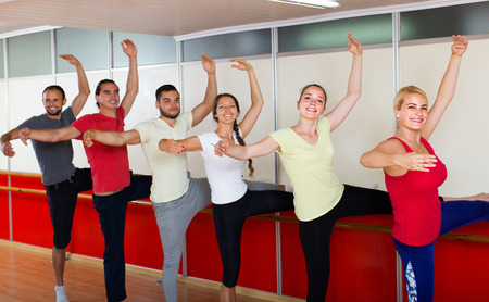 barre: Group of happy men and women practicing at the ballet barre