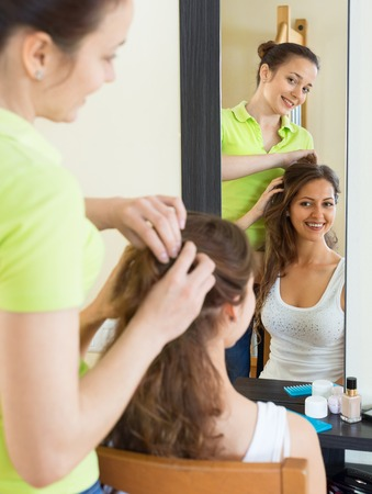 cognate: Young girl doing hairstyle for her girlfriend