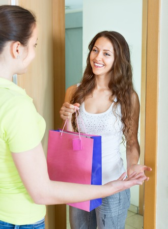 kindred: Cheerful young woman congratulating her friend and gives a gift Stock Photo