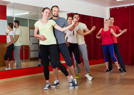 unprofessional: Smiling happy adults dancing bachata together at dance studio Stock Photo