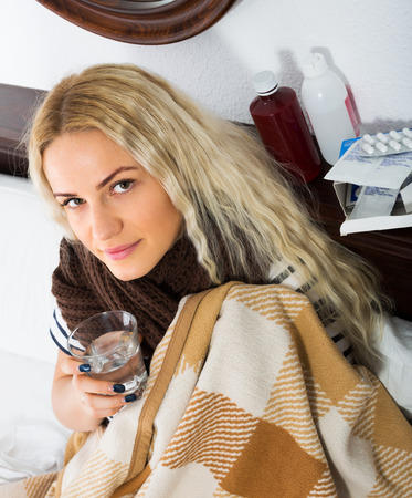 megrim: Young female with fever wrapping herself in scarf indoors Stock Photo