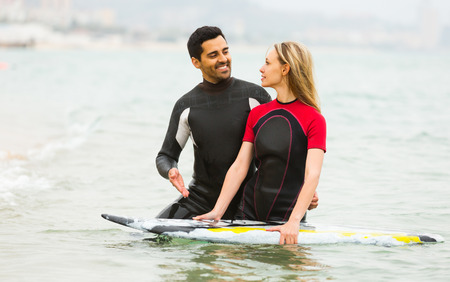waist deep: Young smiling active couple swimming in wetsuits with surf board