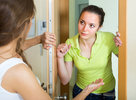 neighbours: Two displeased young female neighbours having conflict at the door