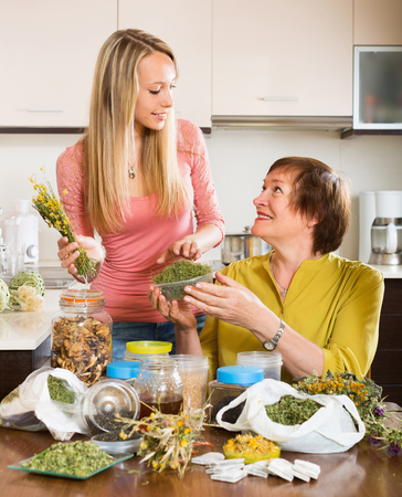 concoct: Smiling mature female with daughter with dried herbs