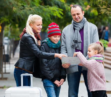 middle class: Feliz familia de clase media de cuatro comprobación dirección en un mapa Foto de archivo