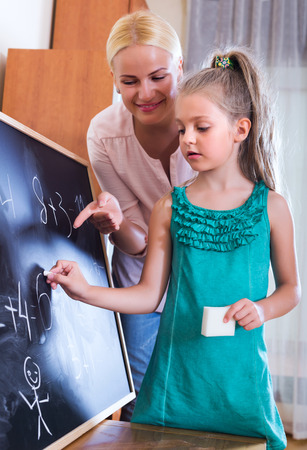 introducing: Positive adult woman introducing numbers to small girl at home Stock Photo