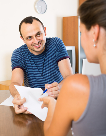 financial planning married: Insurance spanish agent helping client to choose the product indoors
