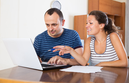 financial planning married: Adult couple sitting at a desk with papers and laptop