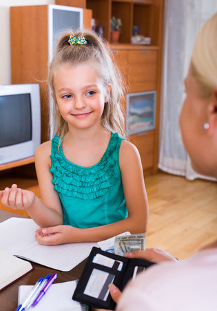 allowance: Allowance of pocket money: cute smiling little girl and mother with purse