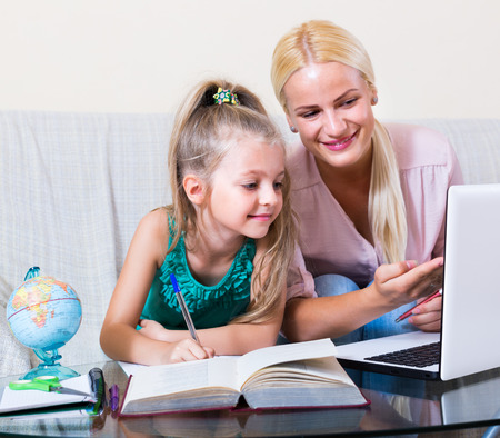 8 years: Private teacher and little girl 8 years old studying with notes at home