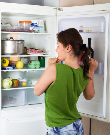 refrigerator kitchen: Adult woman looking for eat in refrigerator at domestic kitchen Stock Photo
