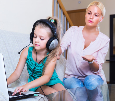internet porn: Frustrated young woman catching her smiling daughter watching forbidden site online