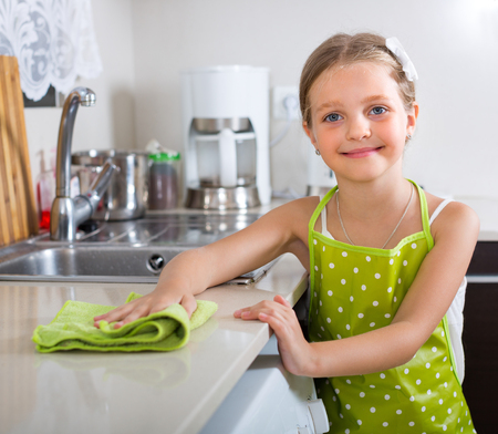 unwashed: Cheerful smiling little girl polishing table top at home kitchen Stock Photo
