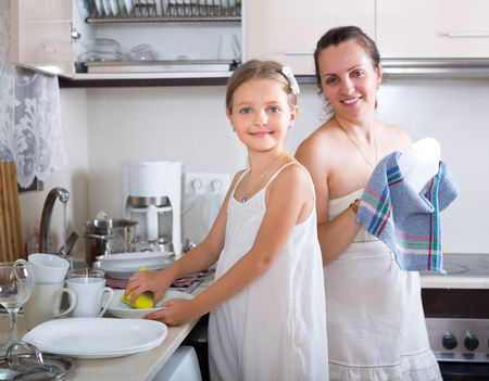 unwashed: Little girl cleaning crockery with mother at domestic kitchen