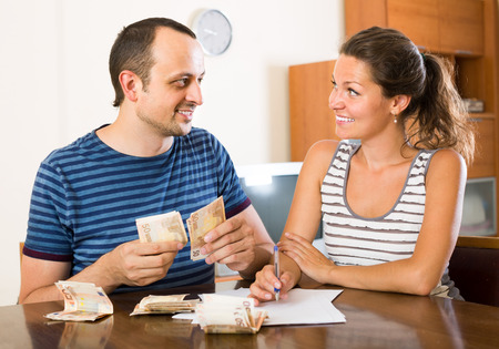 counting money: smiling european woman watching her husband counting money