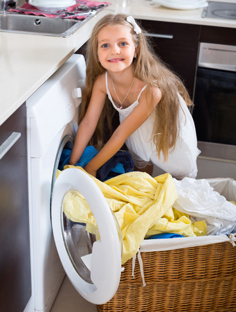 unwashed: Smiling little girl loading washing machine in laundry room Stock Photo