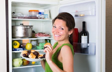 woman eating cake: Smiling woman eating cake from fridge  at home