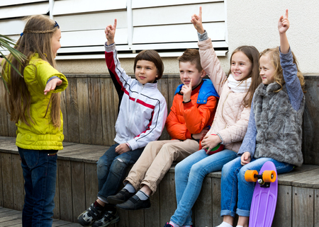 acting: Beautiful little children acting out phrase to friends during charade outdoor