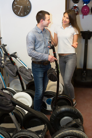rental agency: Kindly male employee helping positive girl to select segway at rental agency
