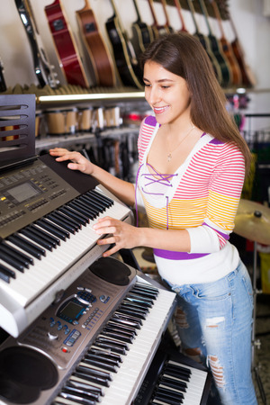 synthesiser: Smiling girl selecting control keyboard for synthesiser in shop