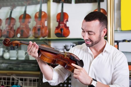 violins: Young positive man with beard purchasing traditional violins in store Stock Photo