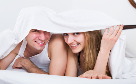 bed sheet: Happy young couple lying in family bed under sheet Stock Photo