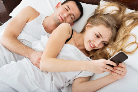 mid distance: Beautiful Wife texting with lover on smartphone while husband is sleeping