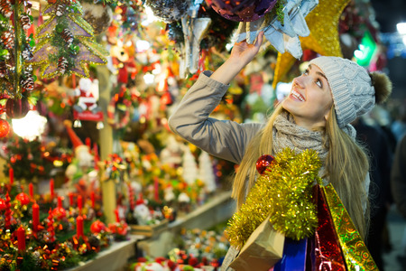 lifestile: Portrait of smiling blonde girl choosing gifts at Christmas market in evening time Stock Photo