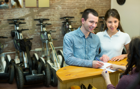 rental agency: Happy young couple selecting a segways at rental agency indoors. Focus on man Stock Photo