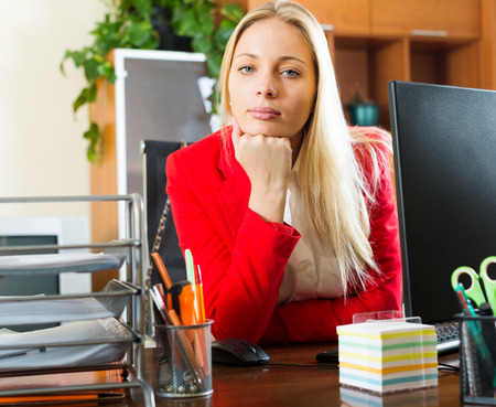 unbearable: Bored businesswoman in red sitting at office desk