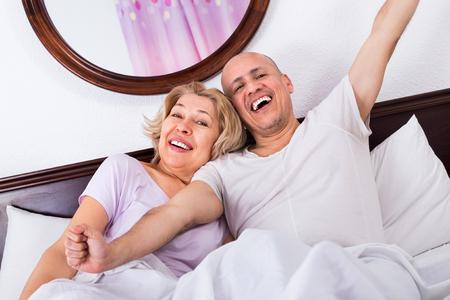 awaking: mature loving couple lounging in bed after awaking cuddling Stock Photo
