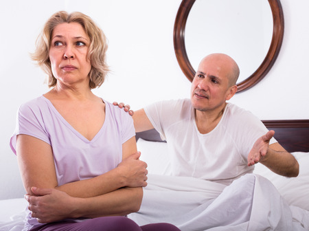 sorting out: Mature angry man and stressed woman sorting out relationships in bed