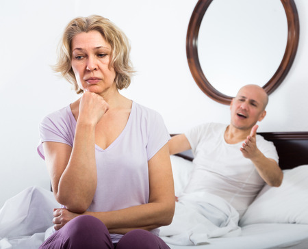 sorting out: Aged man and frustrated  elderly woman sorting out relationships in bed