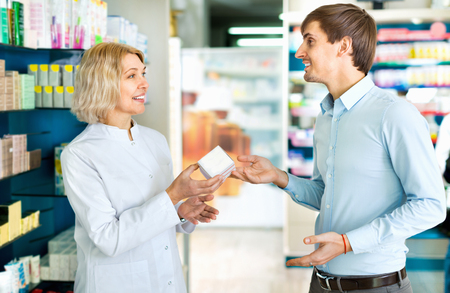 farmacy: Positive female pharmacist counseling customer about drugs usage in modern farmacy