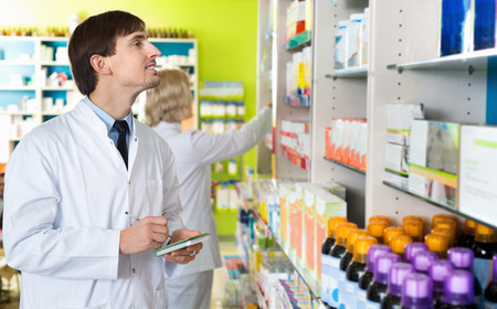 farmacy: Portrait of two friendly charming smiling pharmacists working in modern farmacy Stock Photo