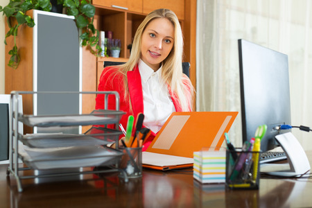 habitual: Young businesswoman writing on her workplace in office