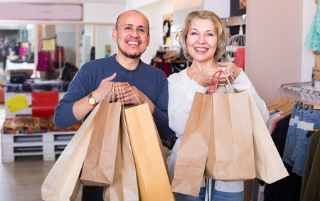 spouses: Mature spouses carrying bags with purchases in clothing discount  store Stock Photo